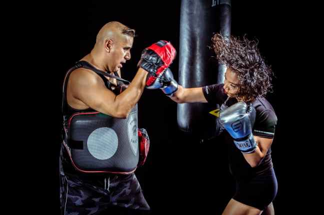 woman punching the hand of man wearing training gloves
